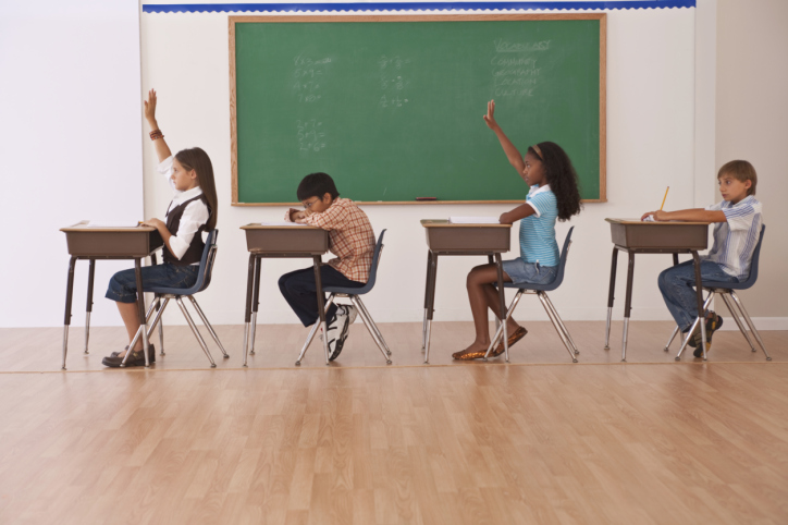 girls raising there hands in classroom while boys are not paying attention