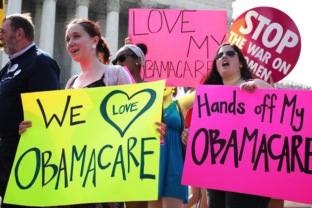 Supporters of Affordable Care Act hold signs